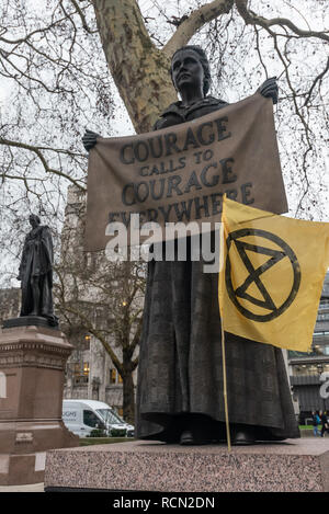 London, UK. 15th January 2019. Millicent Garrett Fawcett with an XR (Extinction Rebellion) flag. Earth Strike UK campaigners in Parliament Square began the first of 4 international actions leading to a global General Strike on 27th September 2019, leaving work & school, boycotting non-necessary consumption and protesting in our streets to demand urgent change to halt global mass extinction, the destruction of our world by catastrophic climate change caused by greenhouse gases, mainly from using carbon fuels, coal, oil and gas. Credit: Peter Marshall/Alamy Live News - Stock Image