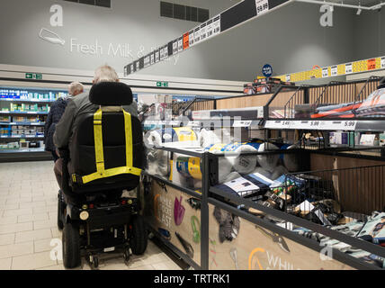 Elderlyperson in mobility scooter shopping in Lidl supermarket. UK - Stock Image