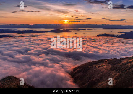 View across Lynn Canal from above Herbert Glacier and Chilkat Mountains at sunset, Southeast Alaska; Alaska, United States of America - Stock Image