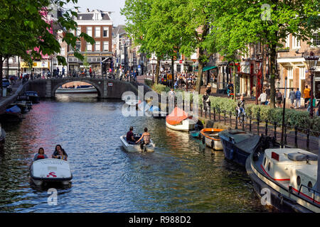 People cycling along Spiegelgracht canal in Amsterdam, Netherlands - Stock Image