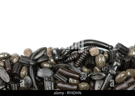 Flat lay overview of sweet and salty, hard and soft licorice on white background. - Stock Image