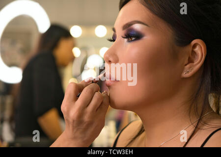 Makeup artist working with Asian model in beauty salon. MUA paints model's lips with contour pencil to make lips more expressive and seductive. Backst - Stock Image