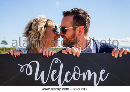 A man and a woman about to kiss over a wooden sign on which he puts the word welcome - Stock Image