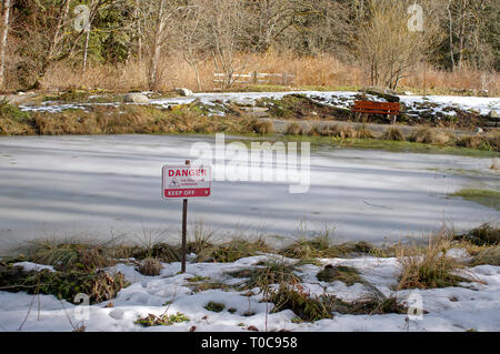 Warning sign reading 'Danger  Ice Thickness Unknown Keep Off' beside an ice-covered pond with a bench on the far side. - Stock Image