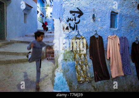 Chefchaouen, Morocco : A child runs at night through the alleyways of the blue-washed  medina old town. - Stock Image