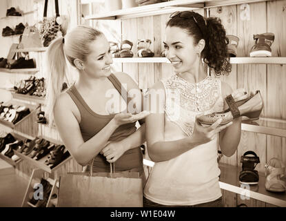 Two smiling young girls holding a paper shopping bags in the boutique - Stock Image