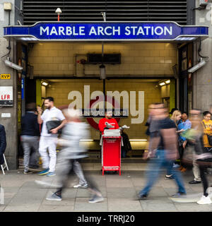 London, England, UK - April 23, 2019: Crowds of commuters walk past the entrance to Marble Arch tube station at rush hour on London's Oxford Street. - Stock Image