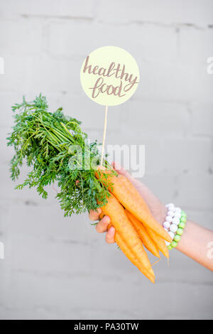 Holding bunch of carrot with green sticker on the gray wall background - Stock Image