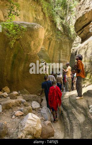 People climbing a short rope, Ol Njorowa gorge, Hells Gate National Park, Kenya - Stock Image