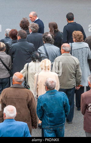 Group of people awaiting funeral parade - France. - Stock Image