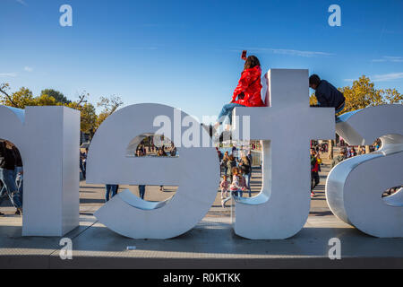 Young woman dressing red jacket making selfi on the top of I amsterdam sign - Stock Image