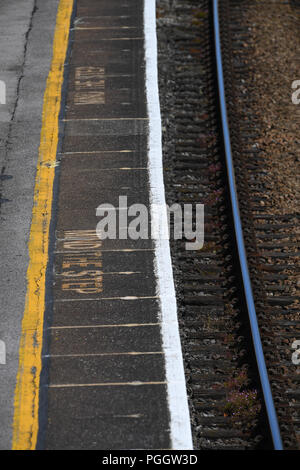 Mind the step warnings on a railway station platform looking from above. - Stock Image