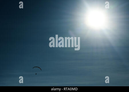 Silhouette of parachutist flying on parachute in the beautiful blue sky. Sun flares. - Stock Image