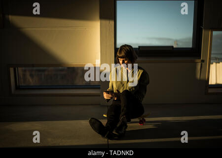 Businesswoman sitting on office floor at sunset, using smartphone - Stock Image