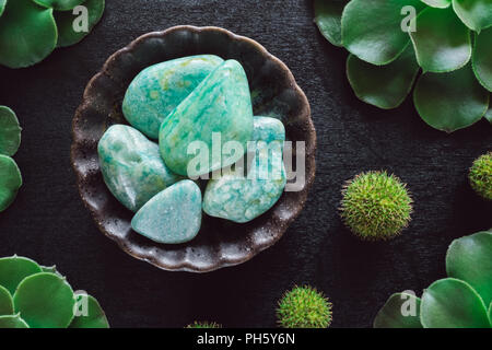 Amazonite with Succulents and Spiky Balls on Black Table - Stock Image