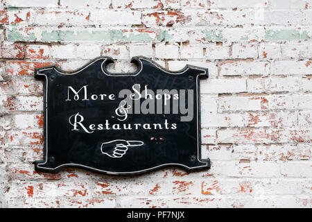More shops and restaurants sign on old white brick wall - Stock Image