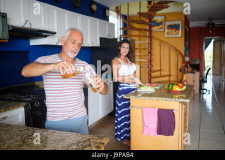 Older man pours himself a glass of beer while the young woman prepares dinner in the kitchen - Stock Image