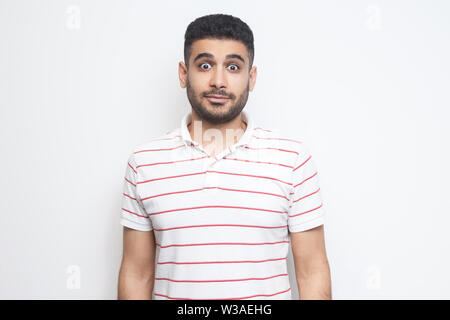 Portrait of surprised handsome bearded young man in striped t-shirt standing with big eyes and looking at camera. indoor studio shot, isolated on whit - Stock Image