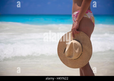woman with hat standing on the beach - Stock Image