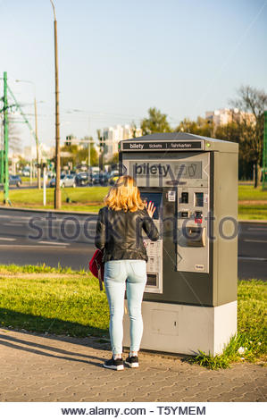 Poznan, Poland - April 18, 2019: Blond woman buying a public transport ticket from a vending machine close by a road in the Rataje station. - Stock Image