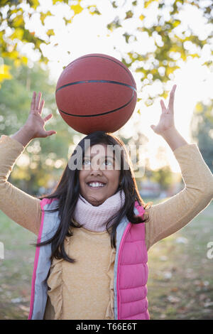 Portrait cute girl balancing basketball on head in autumn park - Stock Image