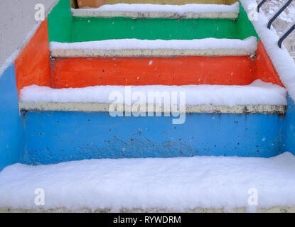 Colorful steps (blue, orange and green) covered in fresh powdery snow - Stock Image
