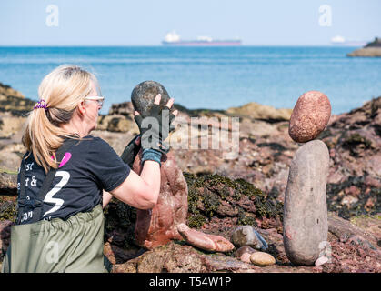 Dunbar, East Lothian, Scotland, UK. 21st Apr 2019. European stone stacking championship:  Caroine Walker balances stones in the   competition at Eye Cave beach on the second day which comprises 2 competitions, a 3 hour artistic challenge and a children's competition. The overall winner receives a trip to llano Earth Art Festival & World Stone Balancing competition in Texas in 2020. Credit: Sally Anderson/Alamy Live News - Stock Image