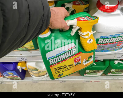 Paris, France - January 25, 2019: Customer buying roundup in a french Hypermarket. Roundup is a brand-name of an herbicide containing glyphosate, made - Stock Image