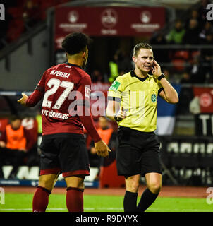 Nürnberg, Germany. 22 December 2018.  Max Morlock Stadion - 22 Dec 2018 - Soccer, 1.Bundesliga - 1.FC Nürnberg vs. SC Freiburg -  Image: (From L-R) Matheus Pereira (1. FC Nürnberg, #27) pleads with the referee as he waits for the video review from an offsides call on a scoring play.  Foto: HMB Media / Ryan Evans Credit: Ryan Evans/Alamy Live News - Stock Image