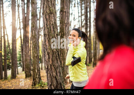 Two female runners with earphones and smartphones in armband jogging outdoors in forest in autumn nature, talking. - Stock Image