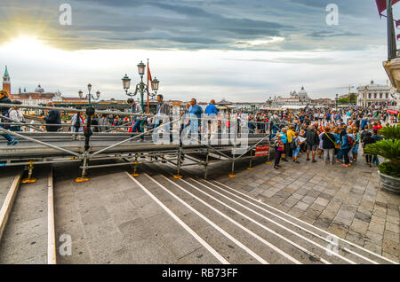 Tourists crowd the market stalls and cafes on a busy day on the waterfront Riva degli Schiavoni promenade along the Grand Canal near St. Mark's Square - Stock Image
