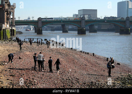 View of River Thames at low tide, school children mudlarking near Queenhithe and Southwark Brige in London EC4 England UK  KATHY DEWITT - Stock Image