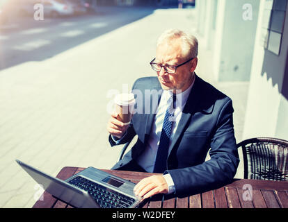 senior businessman with laptop drinking coffee - Stock Image