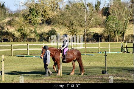 Young horse rider being led around the paddock, Chawton, near Alton, Hampshire, UK. - Stock Image