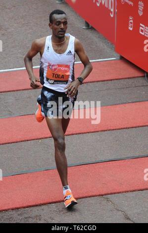 London, UK, 28 April 2019 Tamirat Tola of Ethiopia. Runners at finishing line of  Virgin London Marathon Credit: JOHNNY ARMSTEAD/Alamy Live News - Stock Image