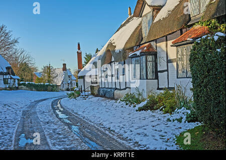 Welford upon Avon, thatched cottages and light snowfall with a blue sky - Stock Image
