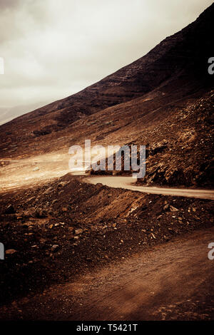 Off road adventure road in the mountains with beach view in wild scenic landscape for alternative travel vacation in the outdoors - cloudy dramatic sk - Stock Image