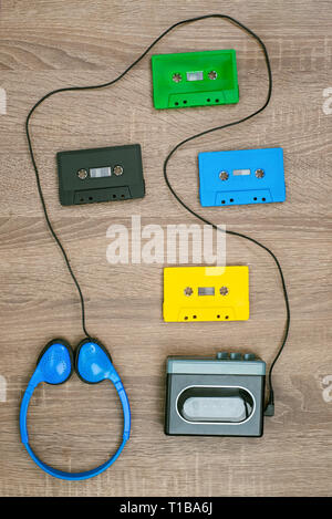 Vintage cassette player, colorful cassete and headphones on the wooden background - Stock Image
