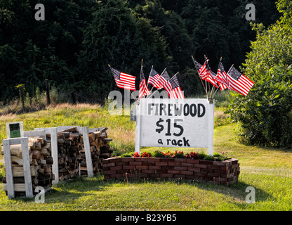 Group of American flags near firewood for sale sign, blowing in the breeze - Stock Image