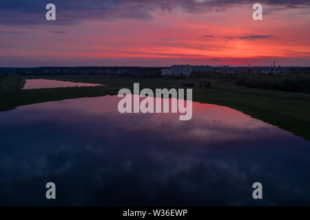 Smooth lakes in the fields of Belarus on a beautiful crimson sunset - Stock Image
