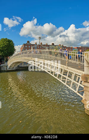 Pedestrians crossing the iconic Ha'penny Bridge over the River Liffey in the centre of Dublin, Ireland - Stock Image