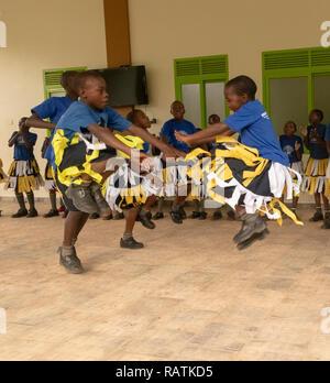 Schoolchildren from Bwindi Junior School performing a dance for tourists before gorilla trekking safari, Bwindi Impenetrable National Park, Uganda - Stock Image