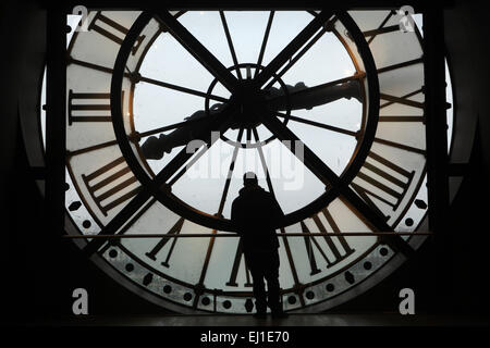 Visitor looks out thought the glass clock in the Musee d'Orsay in Paris, France. - Stock Image