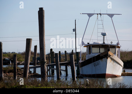 Old rusty shrimp boat tied to pier - Stock Image