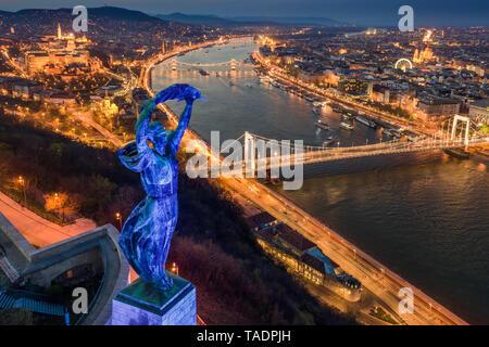 Budapest, Hungary - Blue illuminated Hungarian statue of liberty on World Autism Awareness Day with skyline of Budapest at background at dusk - Stock Image