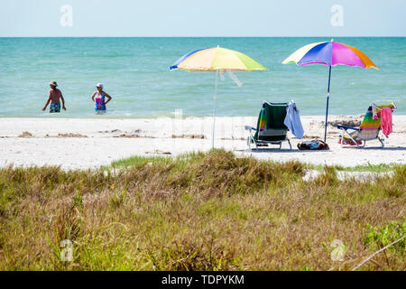 Sanibel Island Florida Gulf of Mexico Coast white sand beach Turquoise color water shoreline umbrellas man woman bathers chairs - Stock Image