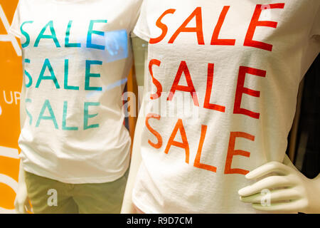 season sale slogan t-shirt on two mannequins in window in shopping mall, red and green color - Stock Image