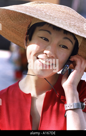 Young woman with mobile phone and large Asian hat - Stock Image