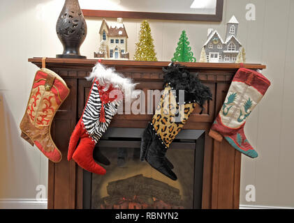 Western boot Christmas stockings hanging over a fireplace. - Stock Image