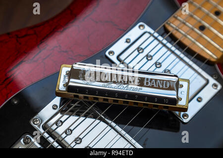 Hohner Marine Band harrmonica on an old electric guitar. Blues, rock music, - Stock Image